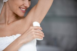 Smiling young woman wrapped in white towel hold applying antiperspirant in armpit